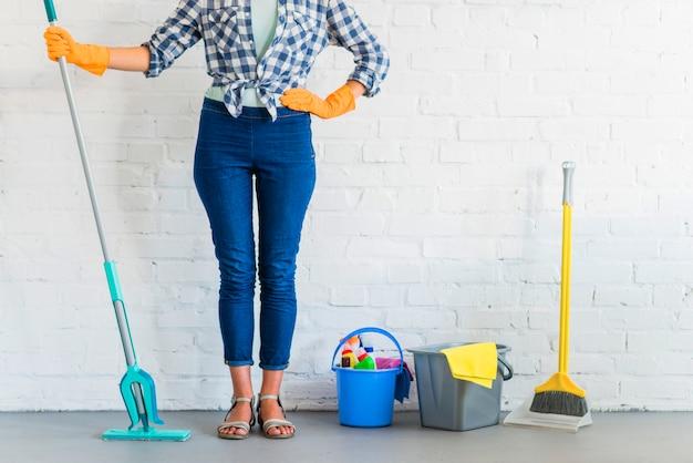 Donna in piedi davanti al muro di mattoni con attrezzature per la pulizia Foto Gratuite