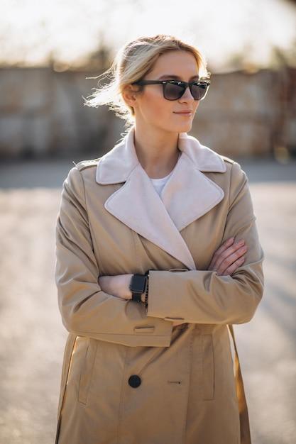 Donna in piedi nel parco in cappotto Foto Gratuite