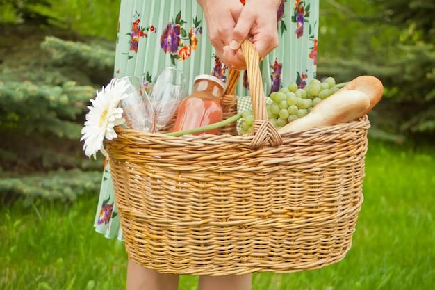 Donna in piedi sull'erba verde e tenendo il cestino da picnic con cibo, bevande e fiori Foto Premium