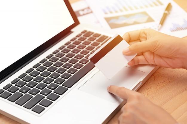 Donna in possesso di una carta di credito e l'acquisto di effettuare il pagamento online tramite computer Foto Premium