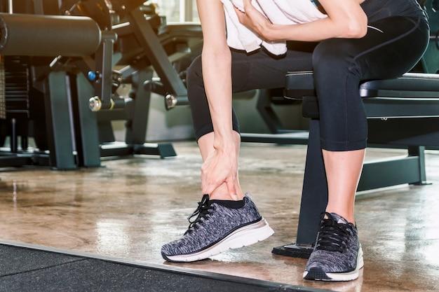 Donna in scarpe da ginnastica che si toccano la gamba e la caviglia nel dolore Foto Premium