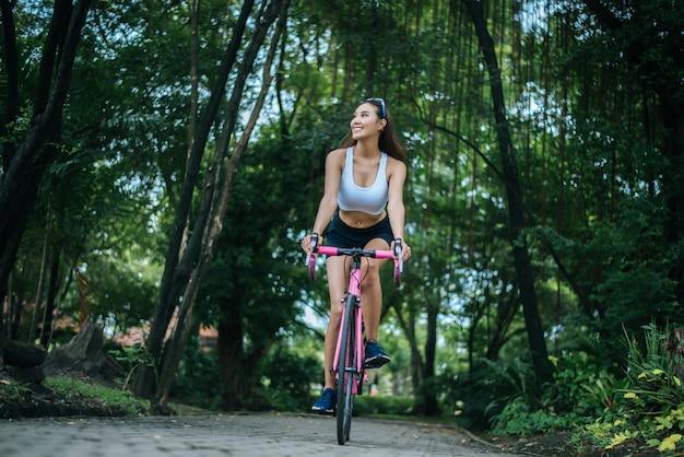 Donna in sella a una bici da strada nel parco. ritratto di giovane donna bella sulla bici rosa. Foto Gratuite