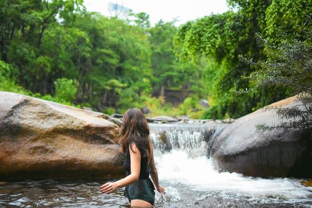 Donna in swimsuite alla giungla e cascata Foto Premium