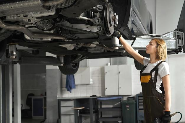 Donna in tuta che ripara i dischi del freno dell'automobile sollevata. Foto Gratuite