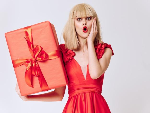 Donna in un bel vestito con scatole regalo in studio, vendita e celebrazione Foto Premium
