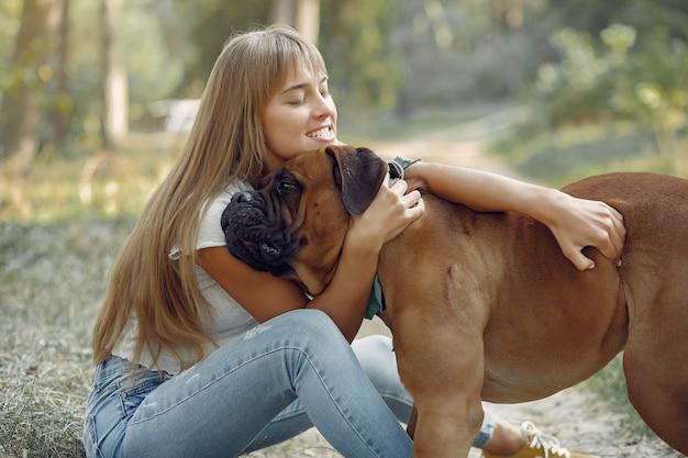 Donna in un bosco estivo a giocare con il cane Foto Gratuite