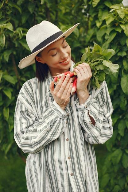 Donna in un cappello che tiene i ravanelli freschi Foto Gratuite