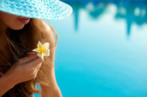 Donna in un cappello di paglia che si rilassa su una sedia a sdraio vicino ad uno stagno lussuoso di estate in hotel, tempo di concetto di viaggiare Foto Premium