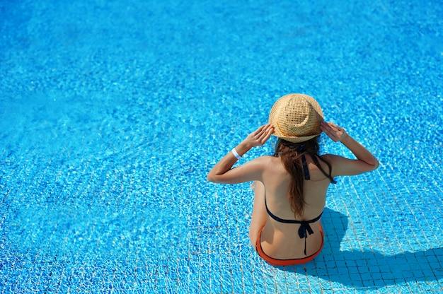 Donna in un cappello di paglia rilassante su una sedia a sdraio vicino a una lussuosa piscina estiva in hotel Foto Premium