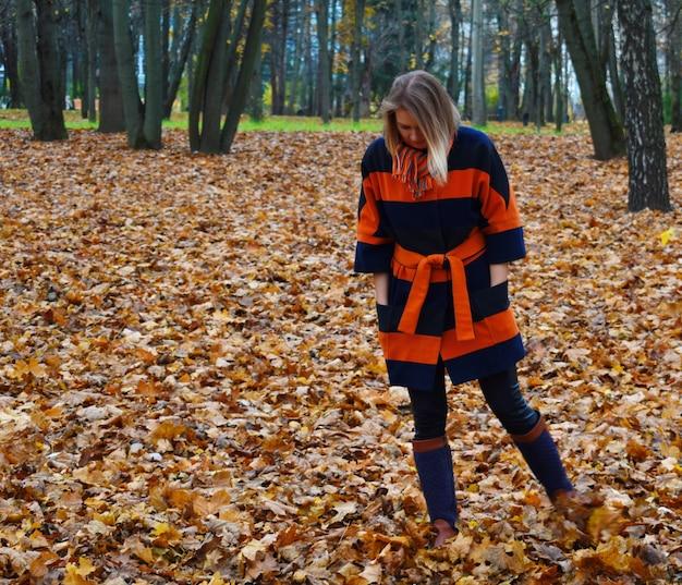 Donna in un cappotto che sta in una foresta Foto Premium