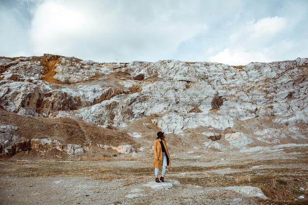 Donna in un cappotto che sta nelle montagne rocciose un giorno di autunno Foto Gratuite
