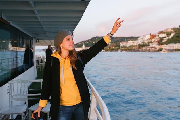 Donna in un maglione giallo e berretto grigio in piedi sul ponte della nave da crociera Foto Premium