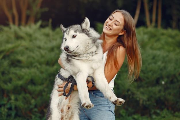 Donna in un parco di primavera che gioca con il cane carino Foto Gratuite