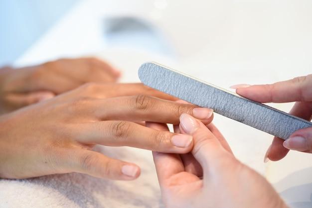 Donna in un salone di unghie che riceve una manicure con lima per unghie Foto Gratuite