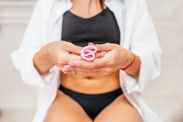 Donna in una biancheria intima nera che tiene una tazza mestruale rosa in sua mano che si siede in una toilette. messa a fuoco selettiva. un'altra opzione per i periodi della donna. Foto Premium