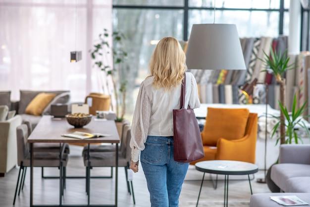 Donna in una camicetta bianca con una borsa bordeaux sulla spalla, in piedi con la schiena nel salone di mobili. Foto Premium