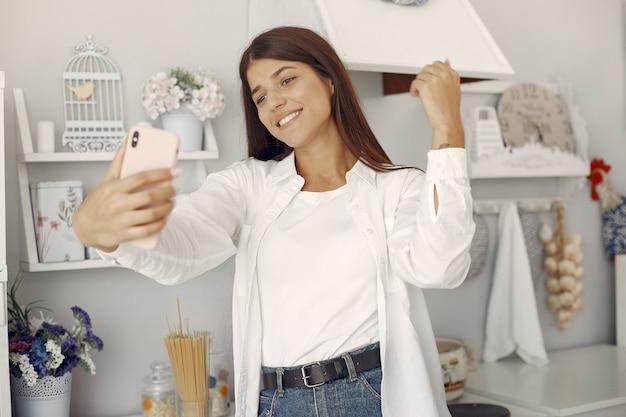 Donna in una camicia bianca che sta nella cucina e che fa un selfie Foto Gratuite