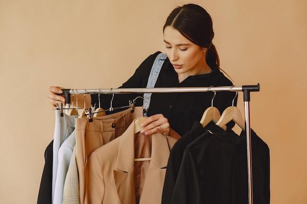 Donna in uno studio con molti vestiti Foto Gratuite