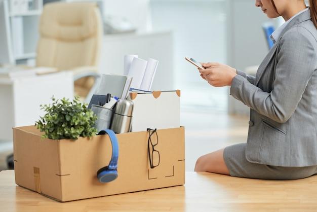 Donna in vestito che si siede sullo scrittorio in ufficio con gli effetti personali in scatola e per mezzo dello smartphone Foto Gratuite