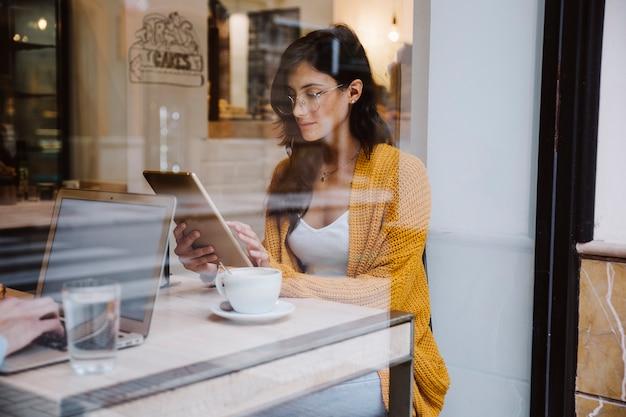 Donna in vetri facendo uso della compressa in caffè Foto Gratuite