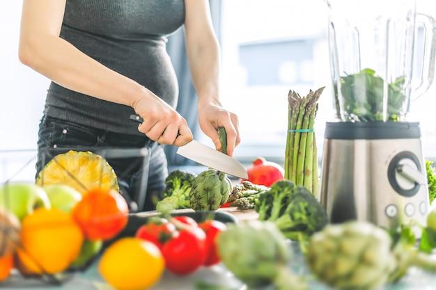 Donna incinta che cucina cibo sano Foto Gratuite