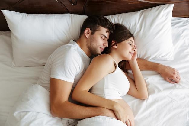 Donna incinta che dorme nel letto con suo marito Foto Gratuite