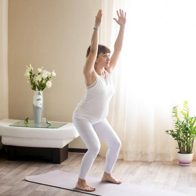Donna incinta che fa utkatasana, yoga della presidenza pongono a casa Foto Gratuite
