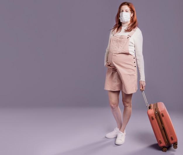 Donna incinta che indossa una maschera protettiva Foto Gratuite