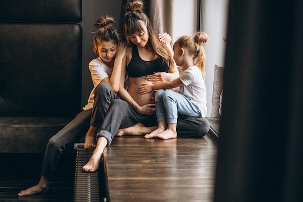 Donna incinta con bambini seduti vicino alla finestra Foto Gratuite