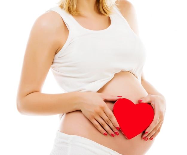 Donna incinta con cuore rosso Foto Premium