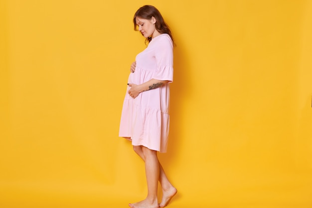 Donna incinta con i capelli annegati, vestito di polvere rosa, che abbraccia la pancia. la femmina elegante e alla moda posa a piedi nudi, guarda il suo addome. concetto di pragnanza e maternità Foto Gratuite