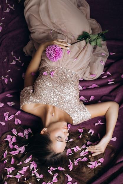 Donna incinta tenera in vestito dentellare che si trova sul plaid viola coperto di petali dentellare Foto Gratuite