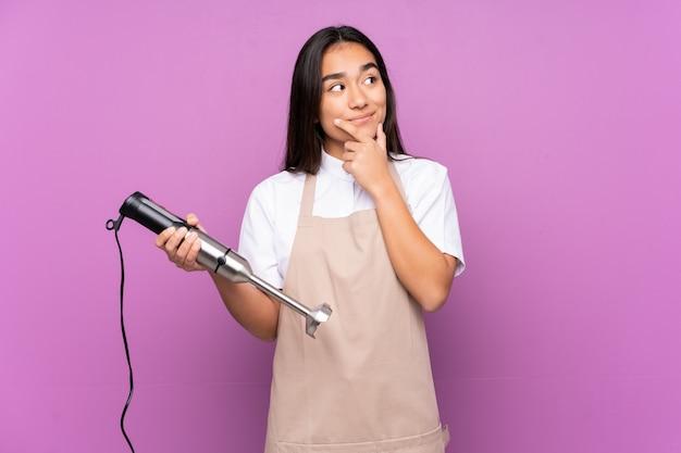 Donna indiana che usando il miscelatore della mano isolato sulla parete viola che pensa un'idea Foto Premium