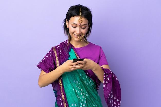 Donna indiana isolata sulla porpora che invia un messaggio con il cellulare Foto Premium