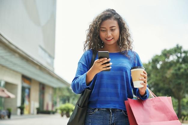 Donna indonesiana che per mezzo dello smartphone durante l'acquisto Foto Gratuite