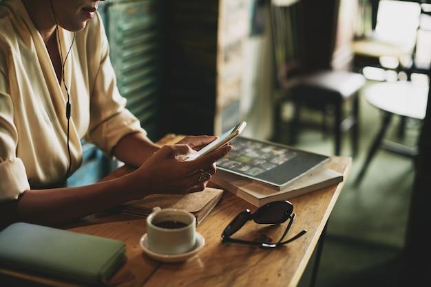 Donna irriconoscibile che si siede nel caffè e che ascolta la musica sullo smartphone Foto Gratuite