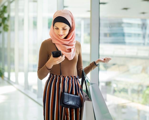 Donna islamica che guarda al telefono Foto Premium