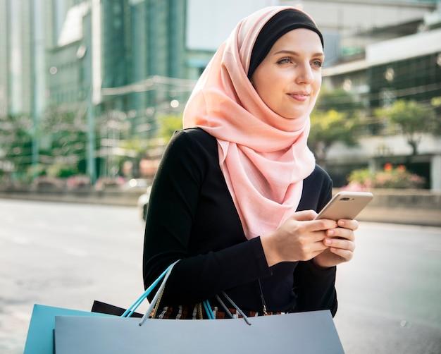 Donna islamica con borse della spesa e tenendo il telefono cellulare Foto Premium