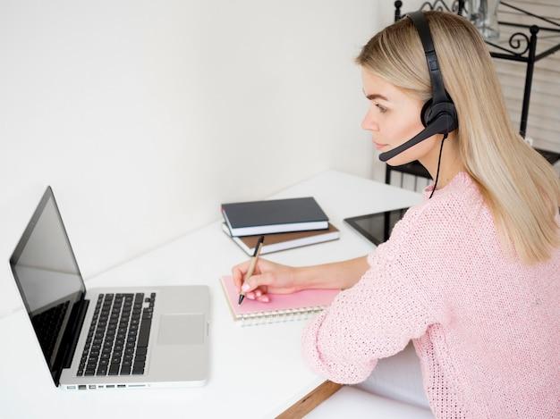 Donna laterale che impara online con le cuffie sopra Foto Gratuite