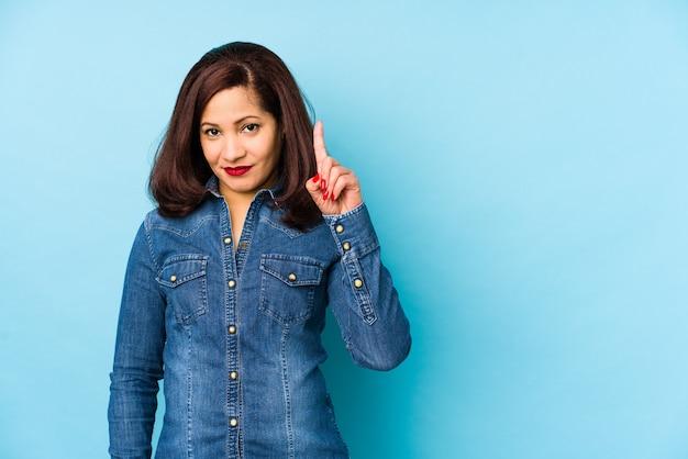 Donna latina di medio evo isolata su una parete blu che mostra numero uno con il dito. Foto Premium