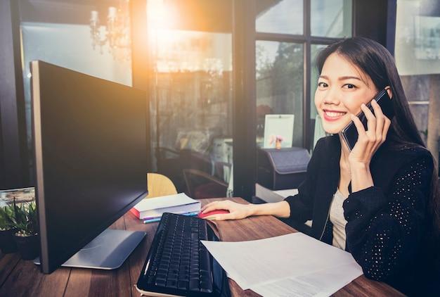 Donna lavoratrice asiatica che utilizza computer nel ministero degli interni e che parla sul telefono cellulare con il fronte di felicità Foto Premium