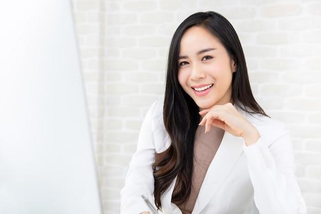 Donna lavoratrice asiatica sorridente in vestito bianco Foto Premium