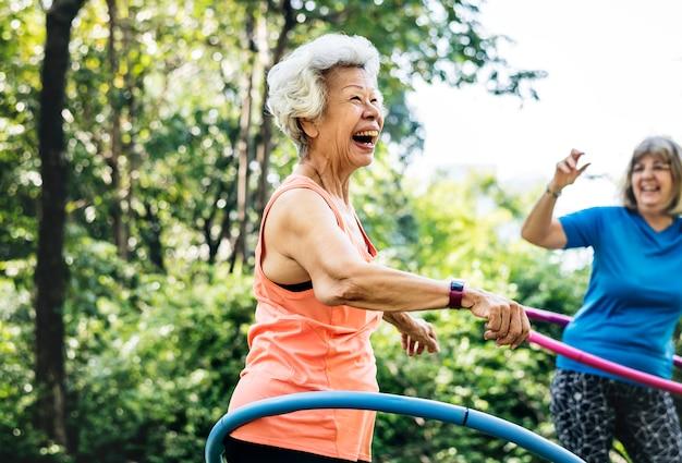 Donna maggiore che si esercita con un hula-hoop Foto Premium