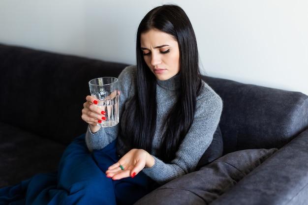 Donna malata abbastanza giovane che tiene una pillola del giorno dopo e un bicchiere d'acqua a casa Foto Gratuite