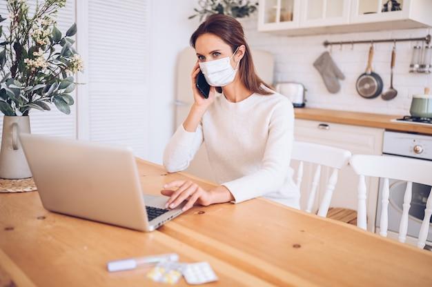Donna malata che indossa una maschera medica, parlando di smartphone e lavorando su un laptop in cucina a casa durante l'isolamento di quarantena pandemia di covid-19 Foto Premium