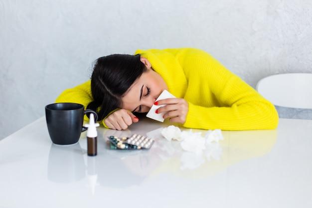 Donna malata con le pillole al tavolo da cucina Foto Gratuite