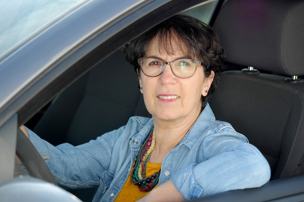 Donna matura castana che conduce automobile Foto Premium