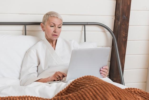 Donna matura che osserva su un computer portatile a letto Foto Gratuite