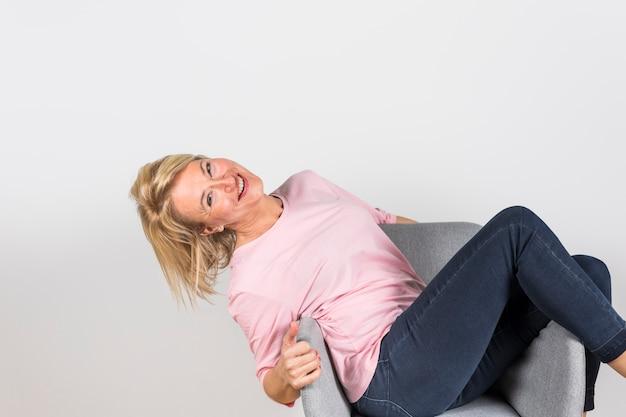 Donna matura sorridente che si siede sulla sedia del bracciolo contro il contesto bianco Foto Gratuite