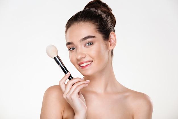 Donna mezza nuda sorridente con la pelle fresca tenendo il pennello per il trucco vicino al viso applicando correttore Foto Gratuite